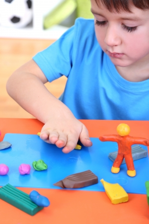 Cute little boy moulds from plasticine on table photo