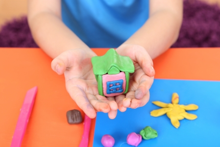 Childs hands holding hand-made plasticine house over desk photo