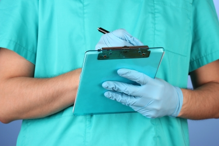 Hand of doctor with pen writing on prescription blank, on blue background photo