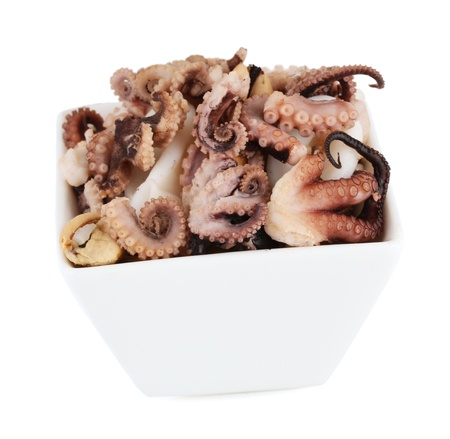 Tentacles of octopus in bowl isolated on white photo