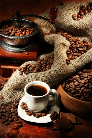 Coffee grinder and cup of coffee on brown wooden background photo