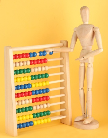 Bright toy abacus and wooden dummy, on yellow background Stock Photo - 17595142
