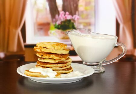 Sweet pancakes on plate with sour cream on table in room Stock Photo - 17595857