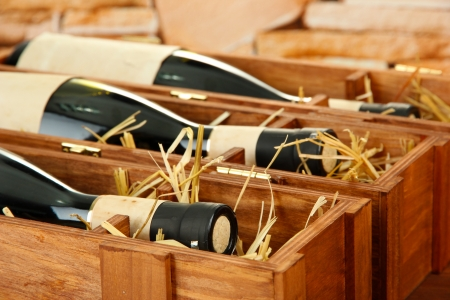 wine gift: Bottles of old red wine in gift wooden box, on stone background