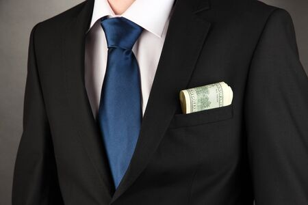 Money in pocket of businessman on black background Stock Photo - 17596147