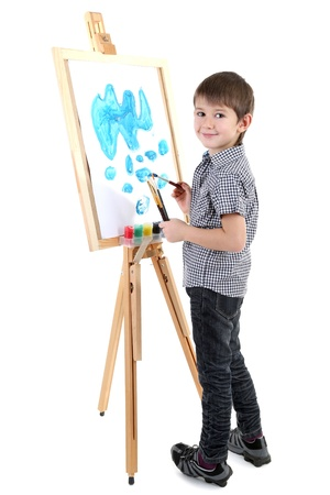 children painting: Little boy painting paints picture on easel isolated on white