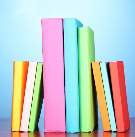 Stack of multicolor books   on blue background photo