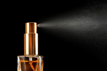 parfum: womens perfume in bottle and spraying, on black background Stock Photo