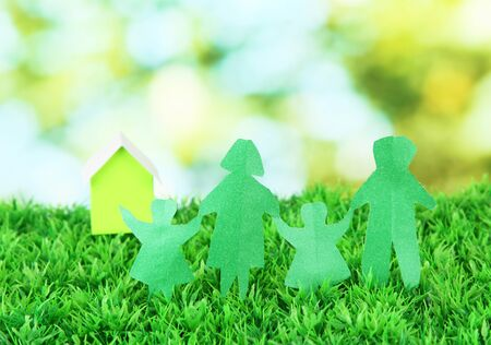 Paper people on green grass on bright background Stock Photo - 17636012