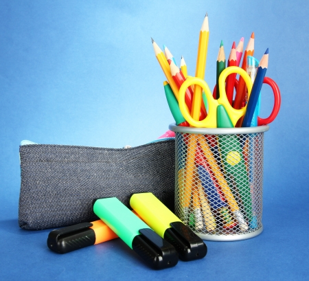 pencil box with school equipment on blue background photo
