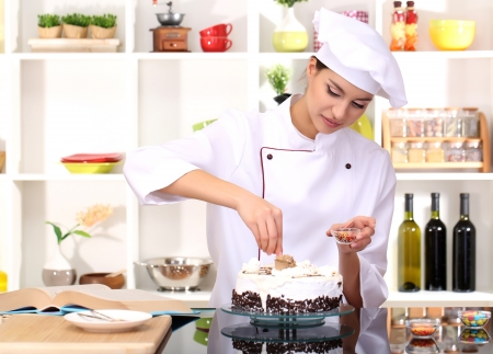 culinary skills: Young woman chef cooking cake in kitchen