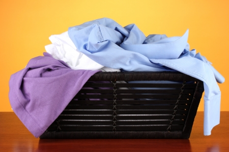 Bright clothes in laundry basket, on color background photo