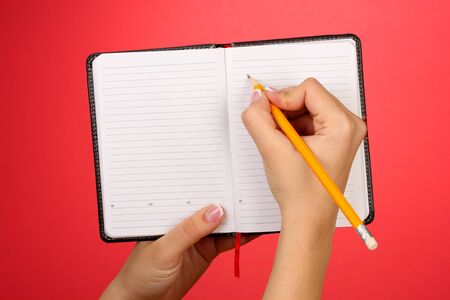Hand write on notebook, on color background Stock Photo - 17644304