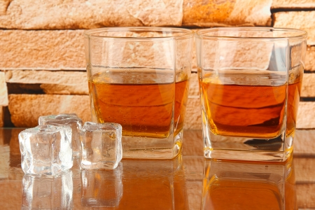 Glasses of whiskey and ice on brick wall background photo
