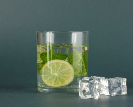 Glass of water with ice, mint and lime on grey background Stock Photo - 17644216