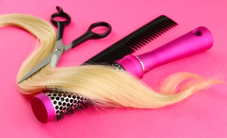 Comb brushes, hair and cutting shears, on pink background photo