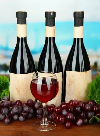 Composition of wine bottles, glass and  grape, on bright background Stock Photo - 17644267
