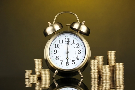 Alarm clock with coins on dark background Stock Photo - 17636039