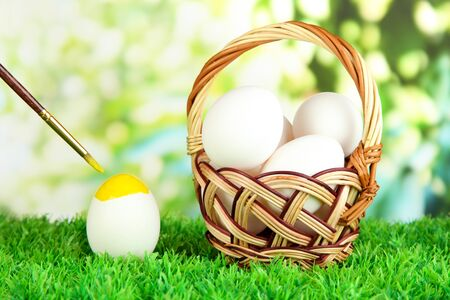 Easter eggs in basket on grass on bright background photo