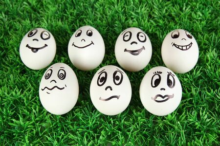 Eggs with funny faces on grass photo