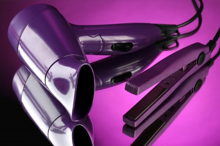 hair drier: Hair dryer and straighteners  on purple background Stock Photo