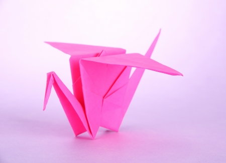 Origami crane on purple background  photo
