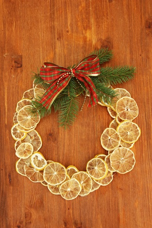 christmas wreath of dried lemons with fir tree and bow, on wooden background photo