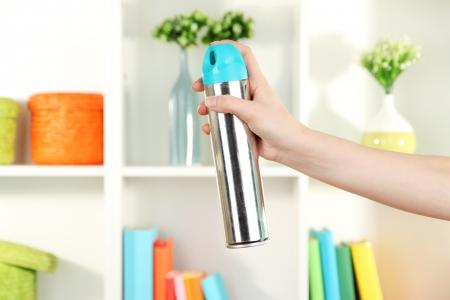 coziness: Sprayed air freshener in hand on white shelves background Stock Photo