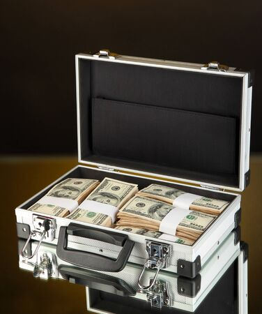 onehundred: Suitcase with 100 dollar bills on dark color background Stock Photo