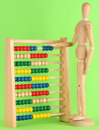 Bright toy abacus and wooden dummy, on green background Stock Photo - 17633797