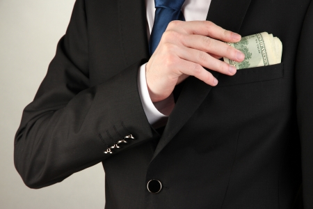 Business man hiding money in pocket on grey background Stock Photo - 17634052