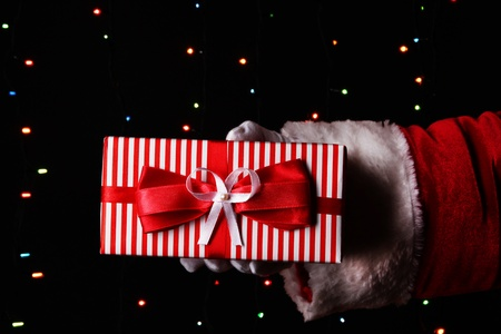 Santa Claus hand holding gift box on bright background Stock Photo - 17644905