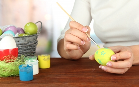 Young woman painting Easter eggs, on bright background photo