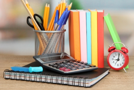 School supplies with books and clock on wooden table photo