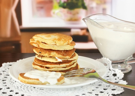 maslen: Sweet pancakes on plate with sour cream on table in room Stock Photo
