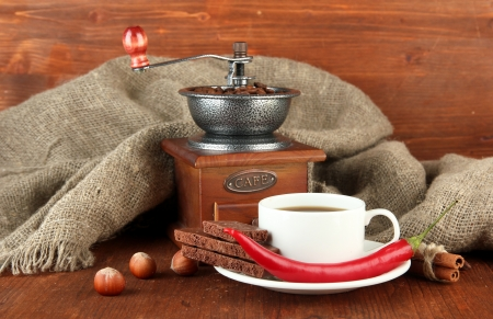 Dark chocolate, hot drink and coffee mill on wooden background photo