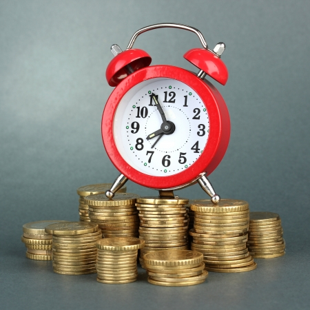 Alarm clock with coins on grey background Stock Photo - 17649808
