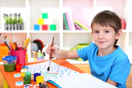 Cute little boy painting in his notebook photo