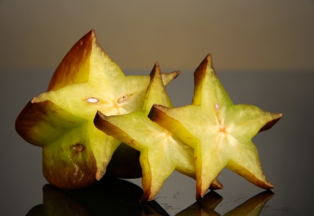 exotics: Two ripe carambolas on yellow background