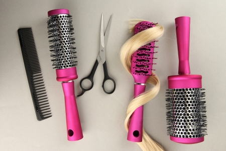Comb brushes, hair and cutting shears, on grey background photo