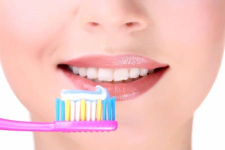 Beautiful young woman with toothbrush close-up photo