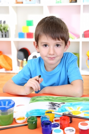 Cute little boy painting in his album photo