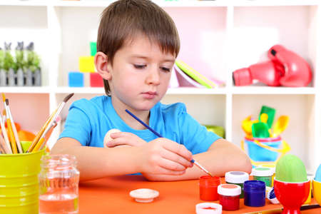 assiduous: Cute little boy painting easter eggs Stock Photo