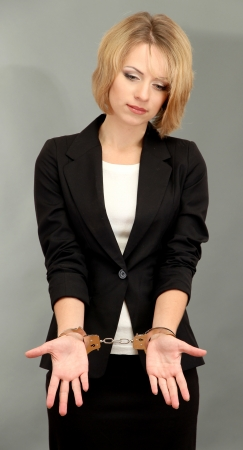 handcuffs: Young beautiful business woman in handcuffs on grey background Stock Photo
