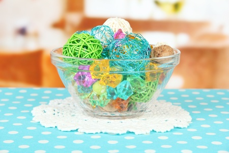 Dried oranges, wicker balls and other home decorations in glass bowl, on bright background photo