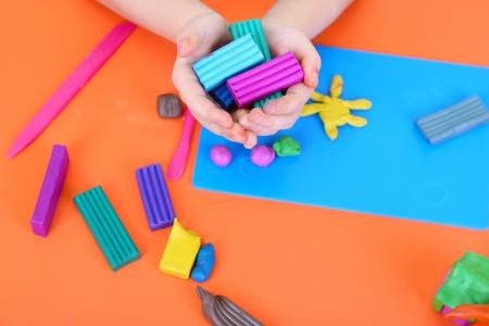 Mains de l'enfant tenue en pâte à modeler sur le bureau de Banque d'images