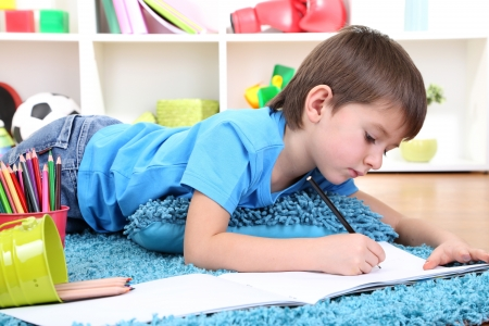 Cute little boy drawing in his album photo