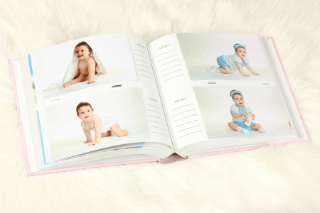 baby open present: Open photo album with pictures on white carpet