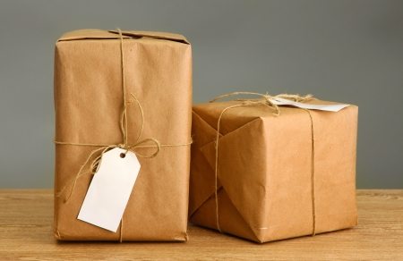parcels boxes with kraft paper, on wooden table on grey background photo