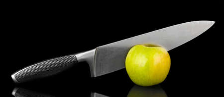 Green apple and knife on isolated on black photo